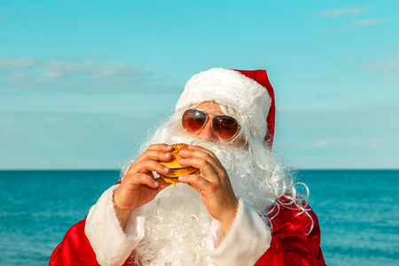 Santa Claus on the beach eating a hamburger. The concept of unhealthy eating. Stock Photo