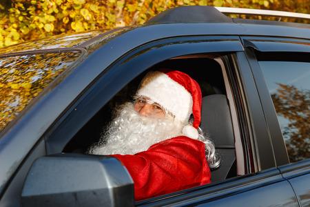 Authentic Santa Claus. Santa Claus drives a car through the autumn forest. Waiting for Christmas.