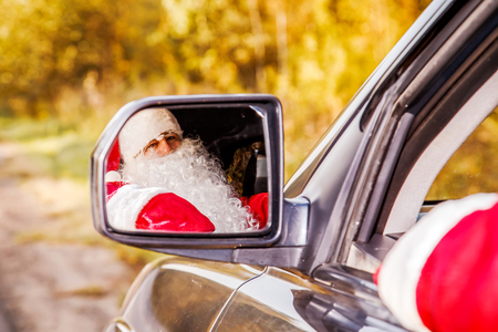 Authentic Santa Claus. Santa Claus drives a car through the autumn forest. Waiting for Christmas. Stock fotó - 87404224