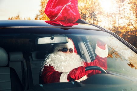 Authentic Santa Claus. Santa Claus drives a car through the autumn forest. Santa is carrying gifts.