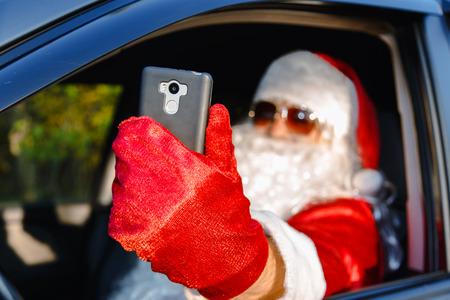 Authentic Santa Claus. Santa Claus makes a selfie in the car. Selective focus.