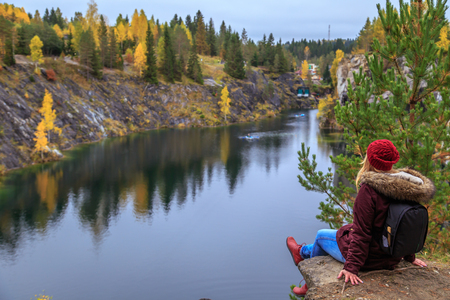 Girl tourist looks at mountain lake in Marble Canyon. Autumn in Karelia, Russia. Stock fotó - 87482267