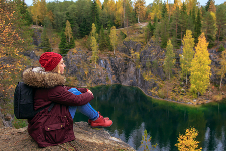 Girl tourist looks at mountain lake in Marble Canyon. Autumn in Karelia, Russia. Stock fotó
