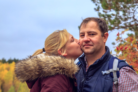 The family of travelers kisses. Autumn in Karelia, Russia. The concept of freedom.