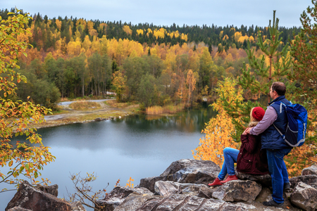 Family travelers looking at a mountain lake in Marble Canyon. Autumn in Karelia, Russia.