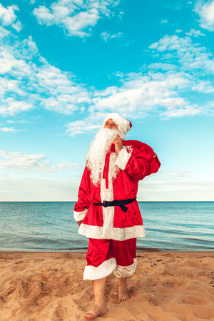Santa Claus with a bag of gifts on the beach. The symbol of Christmas. Stock fotó