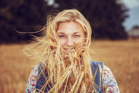 Beautiful blonde girl in a dress in a wheat field. Summer harvest.