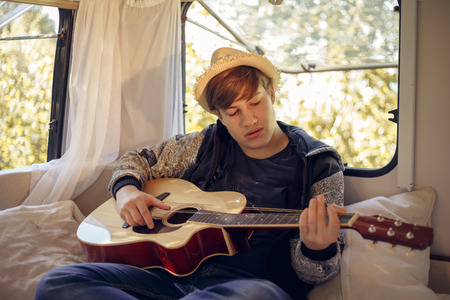 Young traveler with a guitar in his camper van.