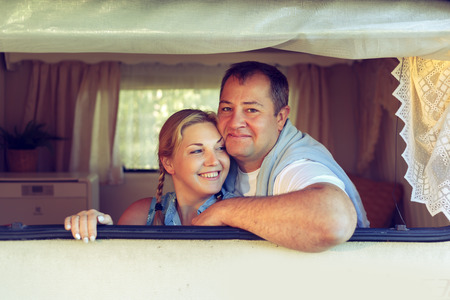 Happy couple of tourists sitting in a camper van on a summer day. Vintage, toned.