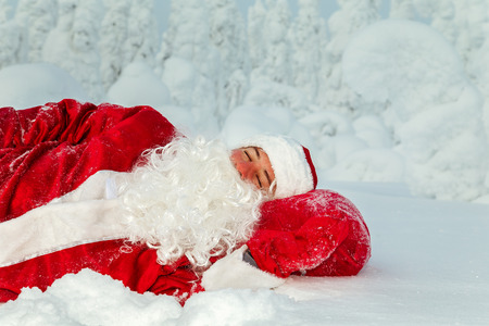 Tired Santa Claus fell asleep in the open air. Magnificent snow-covered landscape.