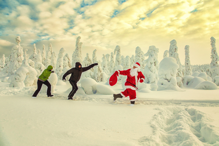 Santa Claus with a bag runs away from people. Motion blur. Magnificent snow-covered landscape. Stock fotó