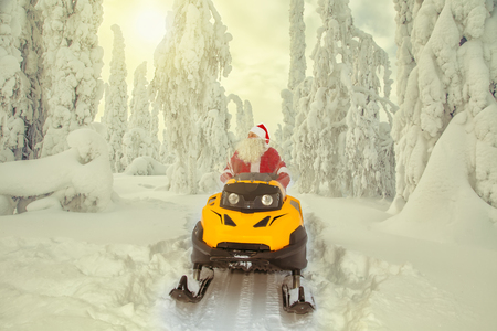 Authentic Santa Claus is riding a snowmobile through the winter forest. Magnificent snow-covered landscape.