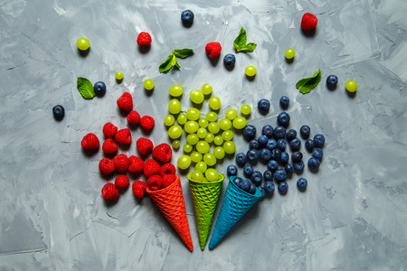 Juicy raspberries, blueberries and grapes in waffle cones on a gray background. Copy space.