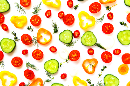 Collection of sliced vegetables and herbs on a white background.