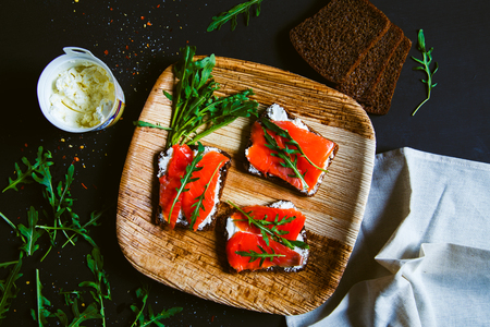Sandwiches with cream cheese, salmon and arugula. Dark background, top view.