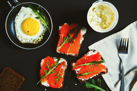 Fried egg and sandwiches with cream cheese, salmon and arugula. Dark background, top view. Stock fotó