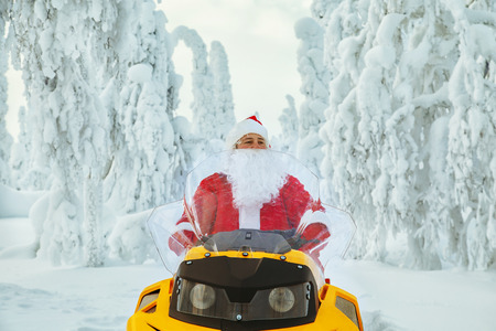 Authentic Santa Claus is riding a snowmobile through the winter forest. Magnificent snow-covered landscape. Stock fotó - 122820907