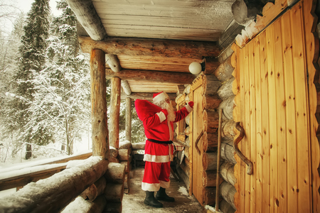 The real Santa Claus knocks on the door of the hut in the winter forest. Stock fotó