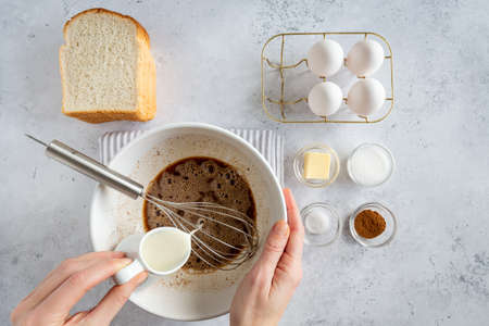 Minimal style flat lay of ingredients for making french toast (or French toast in Dutch) from above on white gray background, woman pouring milk into bowl, view from above