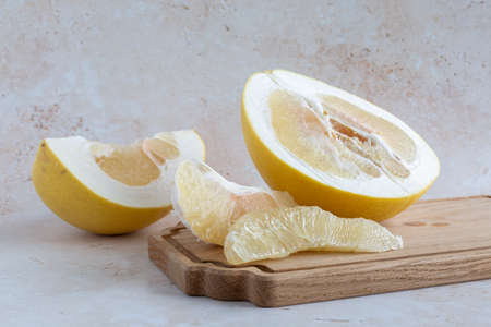 A delicious yellow pomelo sliced open with wedges and a knife on a wooden cutting board on a neutral background, horizontal with copy space