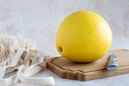 A single delicious yellow pomelo on a wooden cutting board with mesh bag on a neutral background, horizontal with copy space