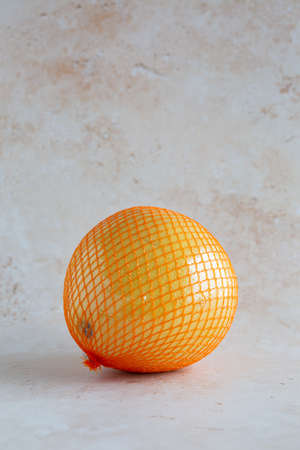 A delicious single yellow pomelo wrapped in a net and plastic foil on neutral background, vertical with copy space