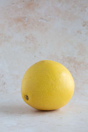 A single delicious yellow pomelo on neutral background, vertical with copy space
