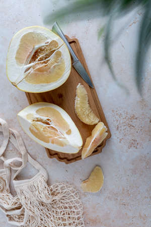 Bird's eye view of sliced yellow pomelo with wedges on a wooden cutting board with mesh bag and bamboo on neutral background with copy space