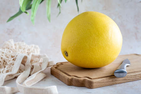 A single whole healthy yellow pomelo on a wooden cutting board with mesh bag on a neutral background, horizontal with copy space