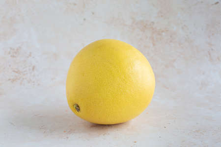 A single delicious yellow pomelo on neutral background, horizontal with copy space