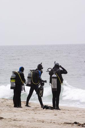 3 つのスキューバダイバーのビーチ ダイビングのための準備 写真素材