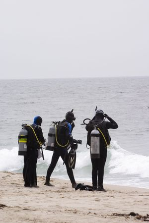 Three scuba divers getting ready for their beach dive