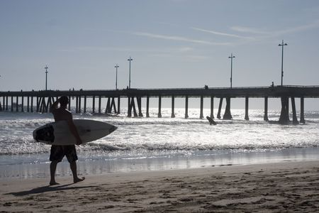 Silhouette of a surfer carrying his surfboard walking along the beach photo