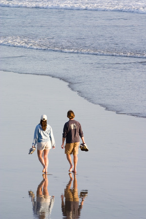 Couple taking an evening walk along the beach photo