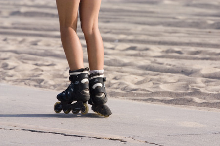 blading: A young woman roller blading along the beach