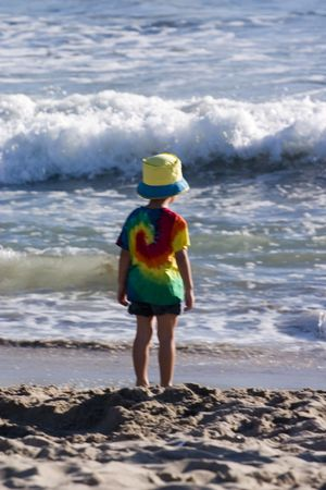 roaring sea: Young child watching the ocean Stock Photo