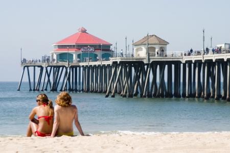 ハンティントンビーチ桟橋の近くに彼はビーチで一日を楽しんでいる若いカップル