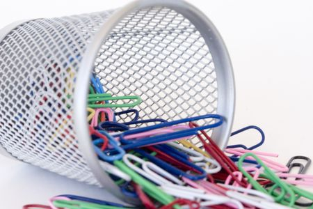 wire mesh: paperclips falling out of the wire mesh container Stock Photo