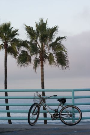 A beach bicycle secured to the boardwalk railing at Manhattan Beach waterfront