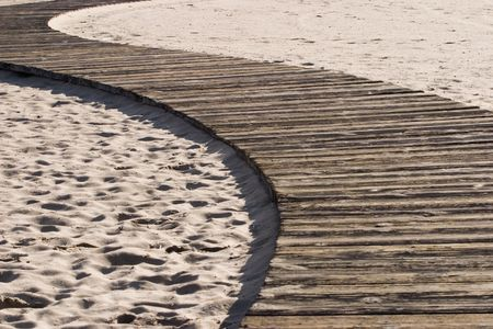 Jogging path lined with old wooden planks on the sand