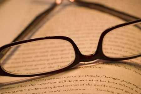 prose: pair of stylish reading glasses and a novel
