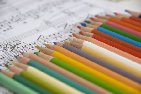 illustrates: color pencils and music scores