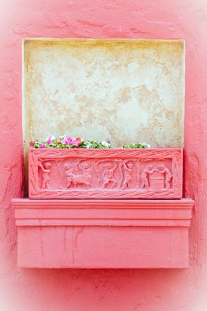 pink planter box on a weathered brick wall photo