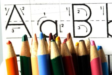多くの色の鉛筆と子供の ABC の学習のパッド