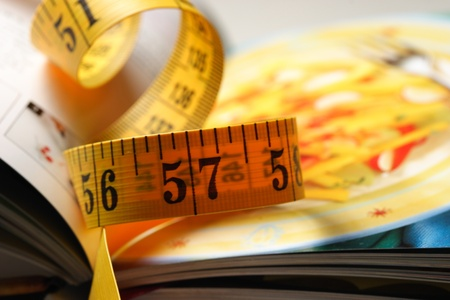 balanced diet: measuring tape on a cookbook