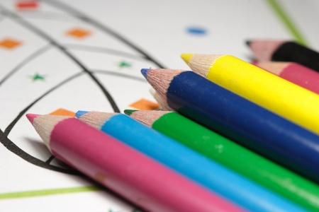 pretty color pencils on coloring book photo