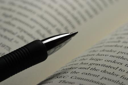 Pluma y un libro sobre la mesa de estudio Foto de archivo - 10465283