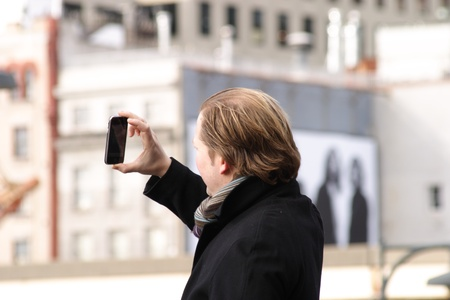 European tourist taking picture with his iPhone