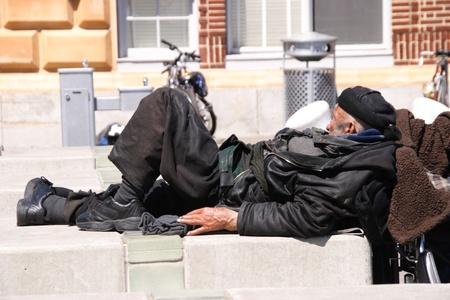 ホームレスの男性は歩道の上で眠っています。 報道画像