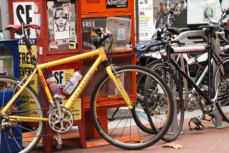 parked bicycles: two bicycles leaning against newspaper vending boxes in the city
